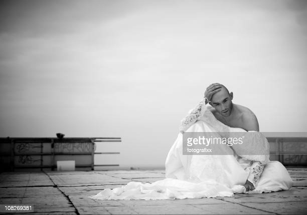 Sad Young Man Sitting on Rooftop Wearing Wedding Dress
