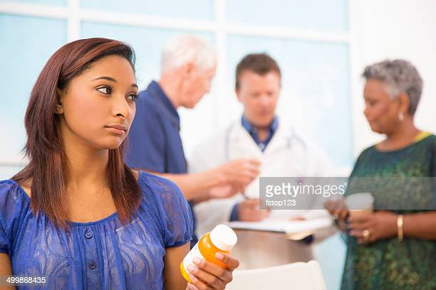 Sad young woman abuses prescription medications. Doctor, patients background.