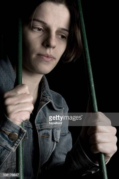 Sad Young Woman Holding On To Bars of Cage