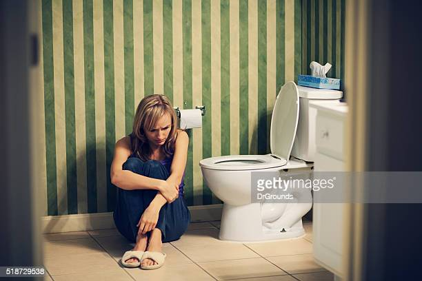 Sad young woman in bathroom
