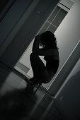 Sad Young Woman Kneeling on Floor, Low Key
