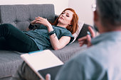 Sad young woman lying on a gray couch in psychologist's office. Coping with loss concept. Blurred therapist in the foreground