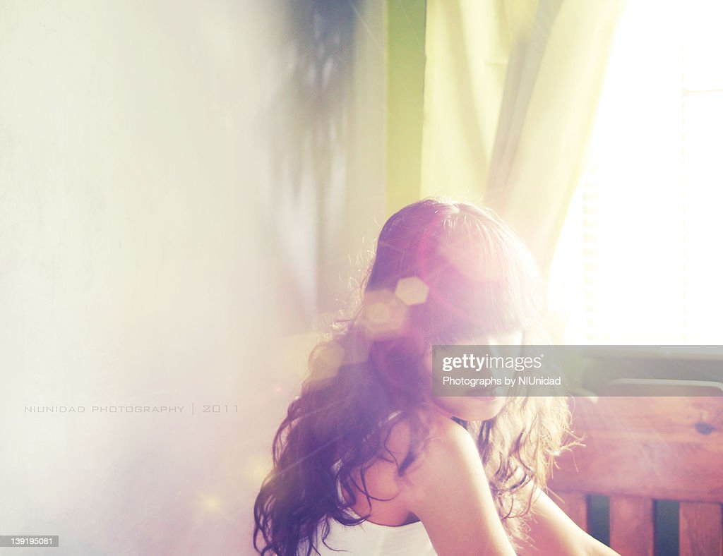 Sad young woman sitting near by window : Stock Photo