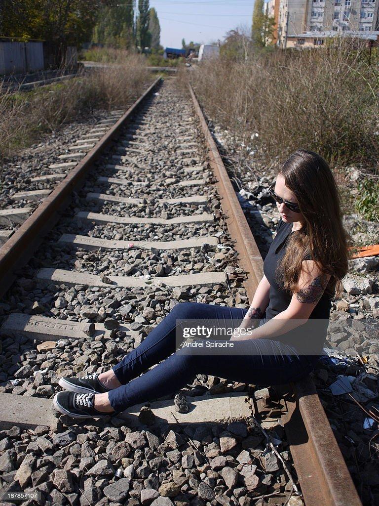 Sad Girl Sitting On Old Suitcase On Rails Stock Photo