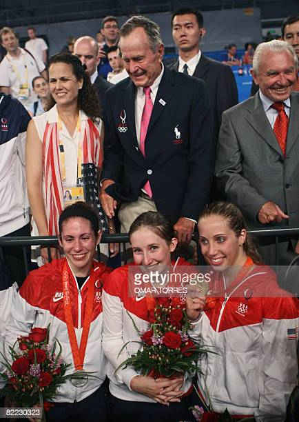 US Sada Jacobson Becca Ward and Mariel Zagunis respectively silver bronze and gold medalist of the women's individual sabre pose eyed by former US...