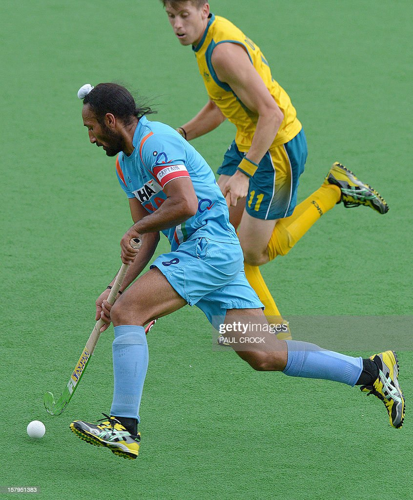 Sadar Singh of India (L) runs with the ball past Eddie Ockenden of Australia during the second semifinal at the men's Hockey Champions Trophy tournament in Melbourne on December 8, 2012. IMAGE STRICTLY RESTRICTED TO EDITORIAL USE - STRICTLY NO COMMERCIAL USE AFP PHOTO / Paul CROCK