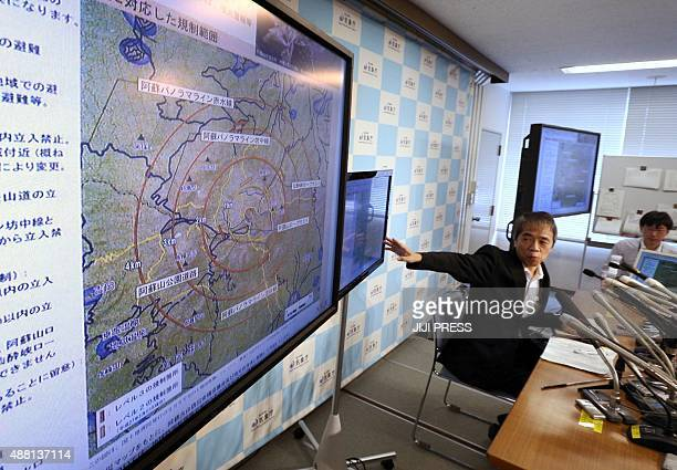 Sadayuki Kitagawa an expert on volcano eruption from the Japan Meteorological Agency shows a map of Mount Aso during a press conference at the JMA...