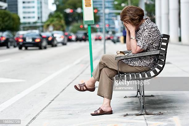 Traurig Frau sitzt alleine in der Stadt.