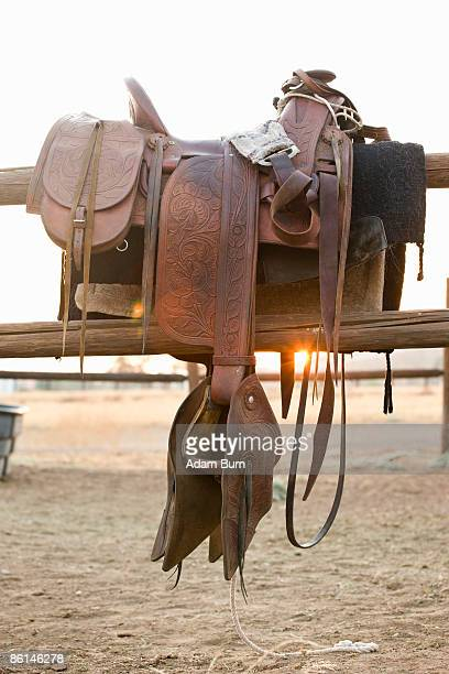 A saddle hanging on a fence
