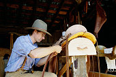 Saddle Maker Working in Barn