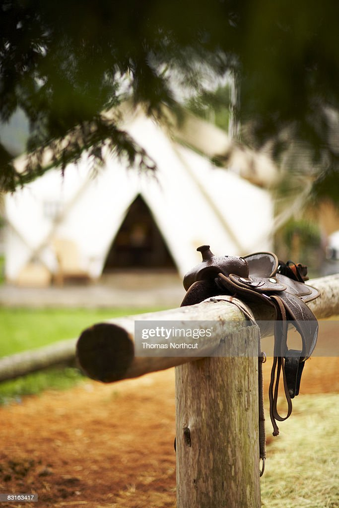 Saddle resting on a hitching post  : Stock Photo