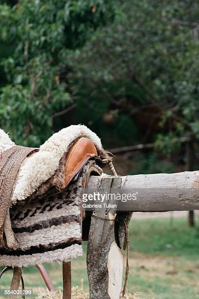 Saddle with stirrups on a rustic fence