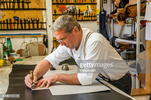 Saddler cutting piece of leather with stencil