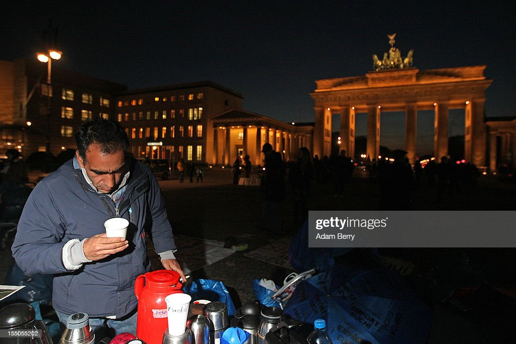 Sadegh Farahani, a refugee from Iran, looks for a tea bag to prepare a cup of tea on the seventh day of a hunger strike in front of the Brandenburg Gate on October 31, 2012 in Berlin, Germany. He and other demonstrators, predominantly from Iran, Afghanistan and Iraq, are subsisting on only water, tea and coffee without sugar. Despite the cold temperatures have been forbidden by the police from having blankets, tents, or isomattresses, as the possession of which would change the official status of the protest, registered in advance, from a 'demonstration' to a 'camp'. They have been sitting in front of the Brandenburg Gate since October 24 and say they will continue their strike until the German government responds to their demands for a halt to deportations and faster processing of asylum applications. Meanwhile the police have been criticized by local party-affiliated as well as non-partisan activist groups for their restrictions.