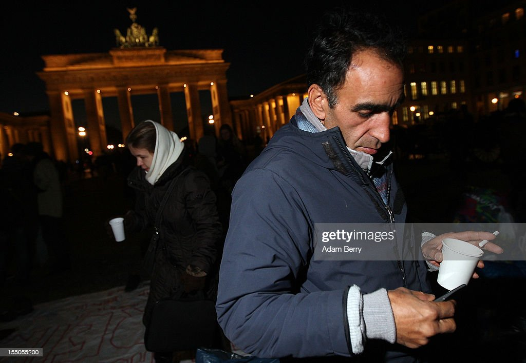 Sadegh Farahani, a refugee from Iran, uses his cell phone while drinking tea and smoking on the seventh day of a hunger strike in front of the Brandenburg Gate on October 31, 2012 in Berlin, Germany. He and other demonstrators, predominantly from Iran, Afghanistan and Iraq, are subsisting on only water, tea and coffee without sugar. Despite the cold temperatures they have been forbidden by the police from having blankets, tents, or isomattresses, as the possession of which would change the official status of the protest, registered in advance, from a 'demonstration' to a 'camp'. They have been sitting in front of the Brandenburg Gate since October 24 and say they will continue their strike until the German government responds to their demands for a halt to deportations and faster processing of asylum applications. Meanwhile the police have been criticized by local party-affiliated as well as non-partisan activist groups for their restrictions.