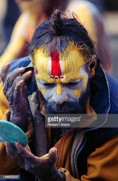 Sadhu (Hindu holy man) applying sacred tilaka marking to his forehead at Pashupatinath Temple.