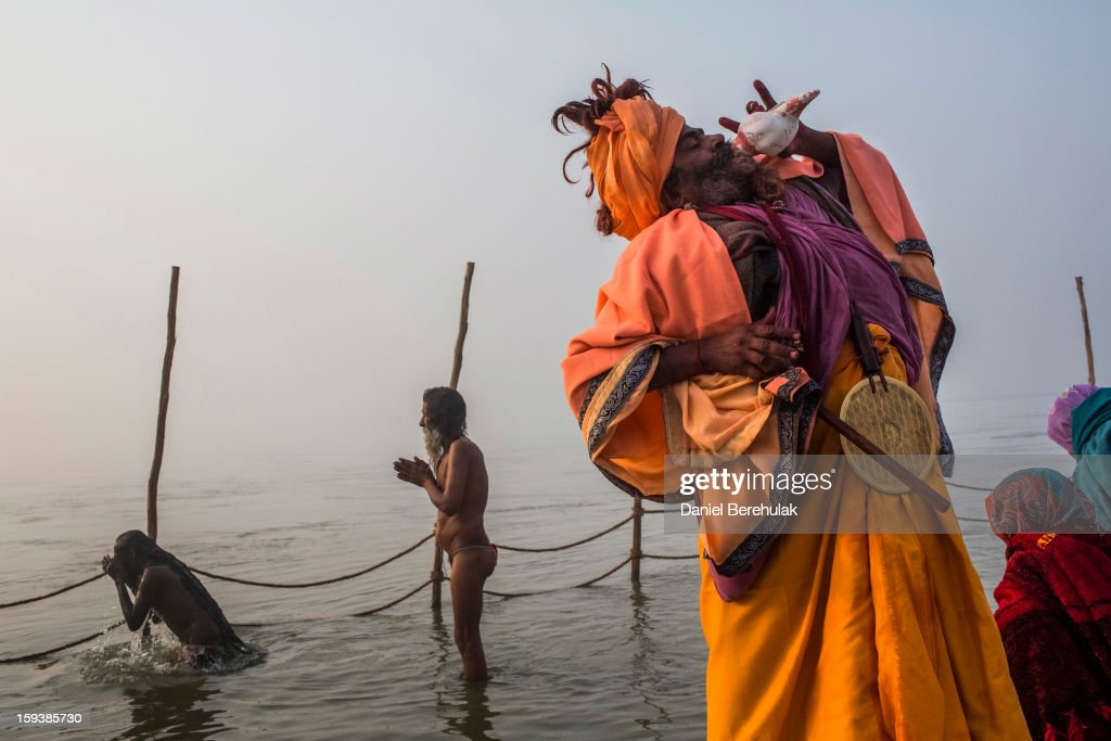 A Sadhu blows a conch shell as other Sadhus or Hindu holy men bathe on the banks of the Ganges river during a procession ahead of the Maha Kumbh Mela on January 13, 2013 in Allahabad, India. The Maha Kumbh Mela, believed to be the largest religious gathering on earth is held every 12 years on the banks of Sangam, the confluence of the holy rivers Ganga, Yamuna and the mythical Saraswati. The Kumbh Mela alternates between the cities of Nasik, Allahabad, Ujjain and Haridwar every three years. The Maha Kumbh Mela celebrated at the holy site of Sangam in Allahabad, is the largest and holiest, celebrated over 55 days, it is expected to attract over 100 million people.