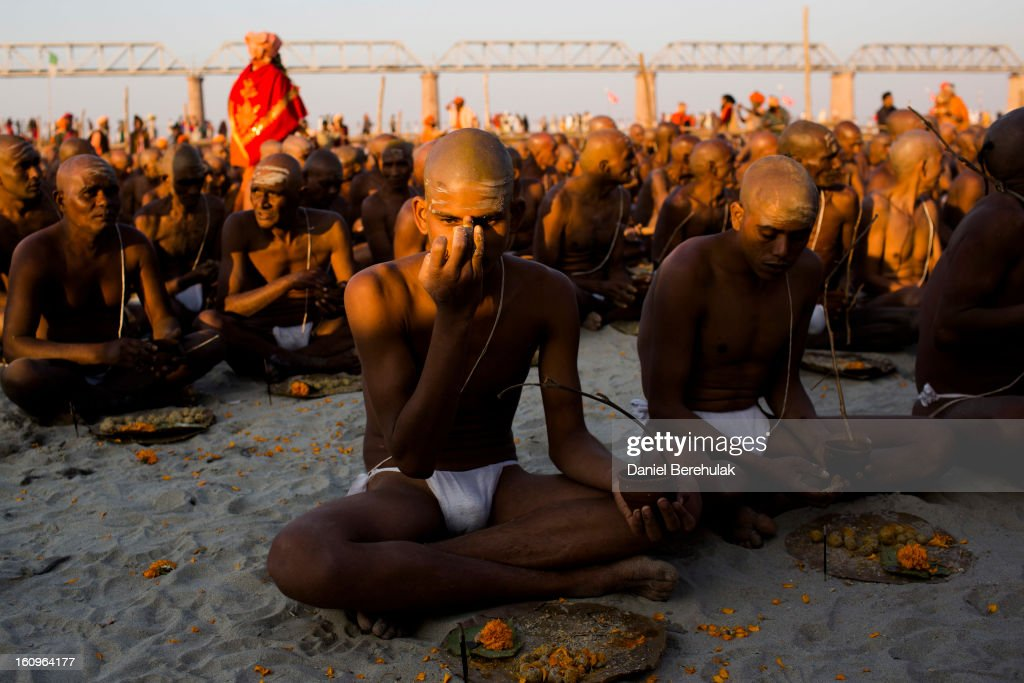 A Sadhu, Hindu holy man, paints mud onto his forehead during an initiation ceremony on the banks of the Ganges river during the Maha Kumbh Mela on February 8, 2013 in Allahabad, India. The Maha Kumbh Mela, believed to be the largest religious gathering on earth is held every 12 years on the banks of Sangam, the confluence of the holy rivers Ganga, Yamuna and the mythical Saraswati. The Kumbh Mela alternates between the cities of Nasik, Allahabad, Ujjain and Haridwar every three years. The Maha Kumbh Mela celebrated at Sangam, is the largest and holiest, celebrated over 55 days, and is expected to attract over 100 million pilgrims who will bathe in holy waters to wash away their sins.