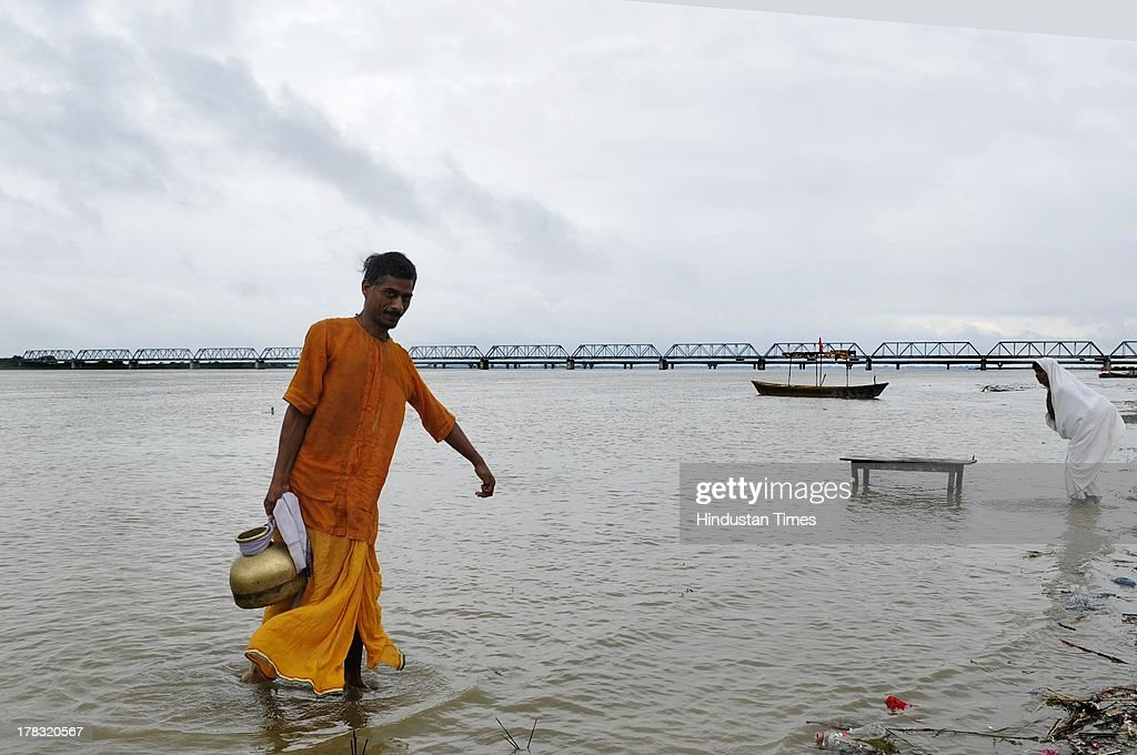 A sadhu holds a container which he filled with holy water at Saryu Ghat on August 28, 2013 in Ayodhya, India. Three days after Vishwa Hindu Parishad (VHP) field Parikarma attempt, Ayodhya saw a heavy presence of security personnel amid Janmashtmi celebrations.