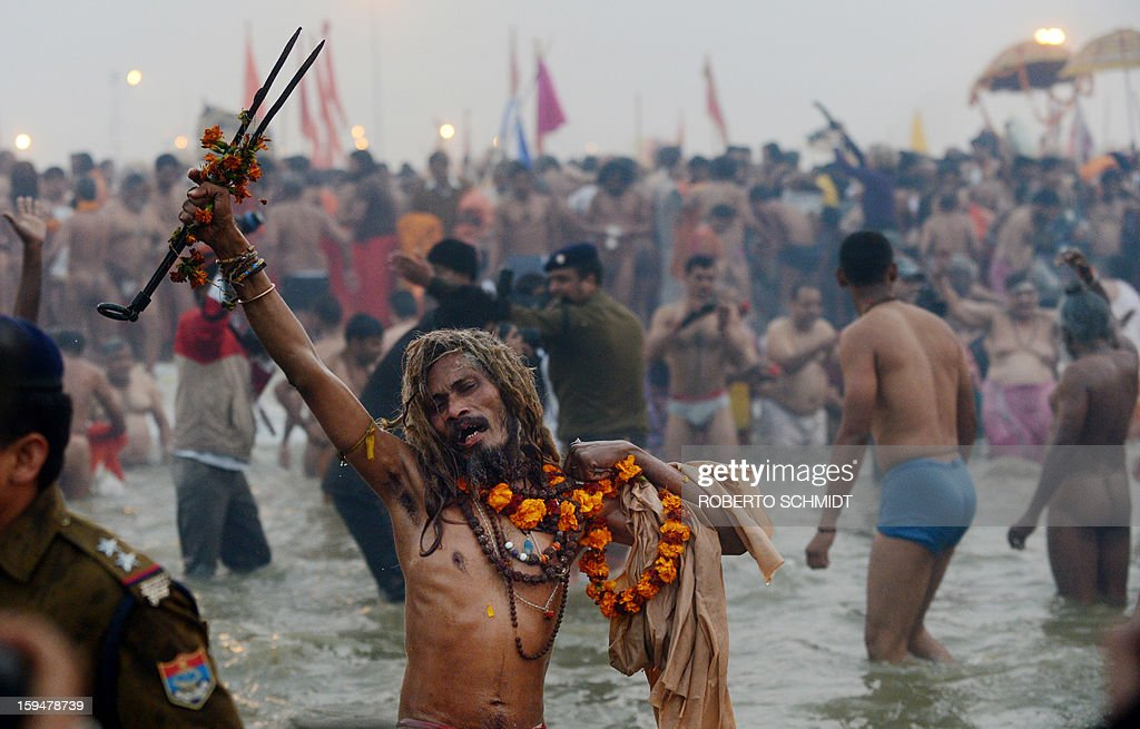 A Sadhu - holy man - bathes with devotees at Sangam, the confluence of the Yamuna and Ganges and the mythical Saraswati rivers during the Kumbh Mela in Allahabad on January 14, 2013. Hundreds of thousands of Hindu pilgrims led by naked, ash-covered holy men streamed into the sacred river Ganges at the start of the world's biggest religious festival. The Kumbh Mela in the Indian town of Allahabad will see up to 100 million worshippers gather over the next 55 days to take a ritual bath in the holy waters, believed to cleanse sins and bestow blessings. AFP PHOTO/ ROBERTO SCHMIDT