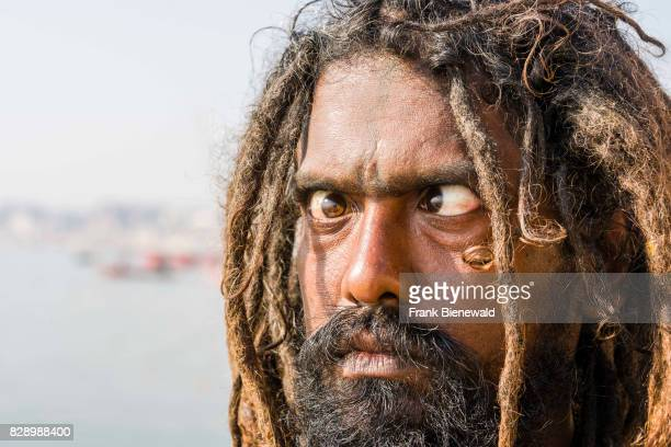 Sadhu holy man is practising eye yoga asana on a platform at the holy river Ganges at Meer Ghat in the suburb Godowlia