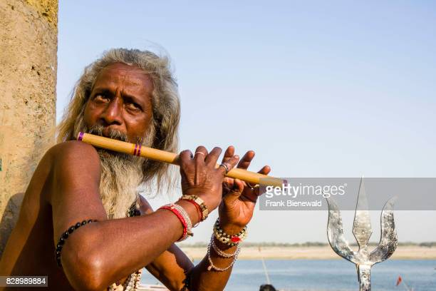 Sadhu holy man is sitting and playing flute on a platform at the holy river Ganges at Dashashwamedh Ghat Main Ghat in the suburb Godowlia