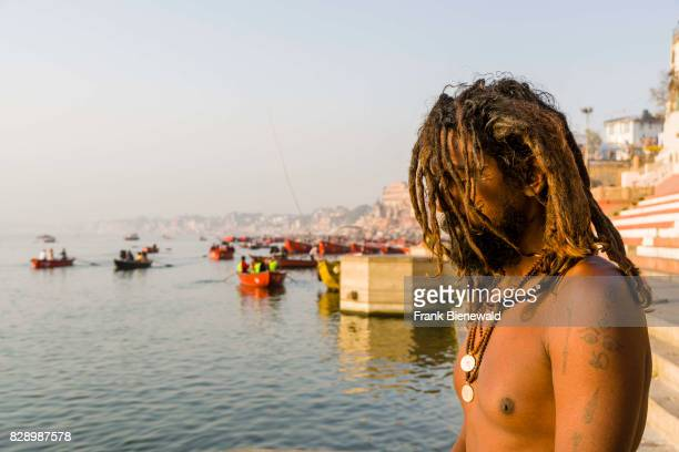 Sadhu holy man is sitting and praying on a platform at the holy river Ganges at Meer Ghat in the suburb Godowlia
