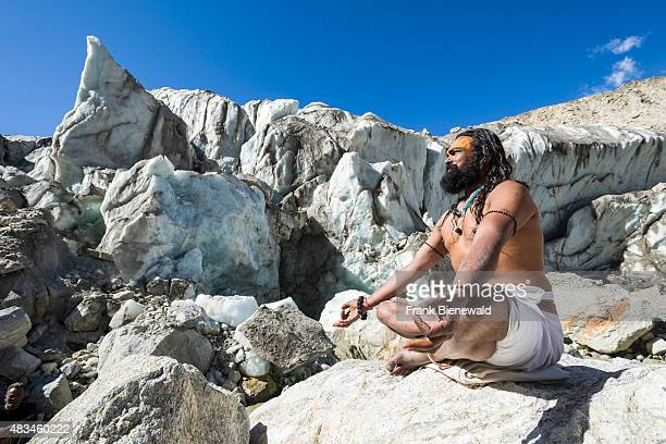 Sadhu holy man is sitting in lotus pose padmasana on a rock at Gaumukh the main source of the holy river Ganges