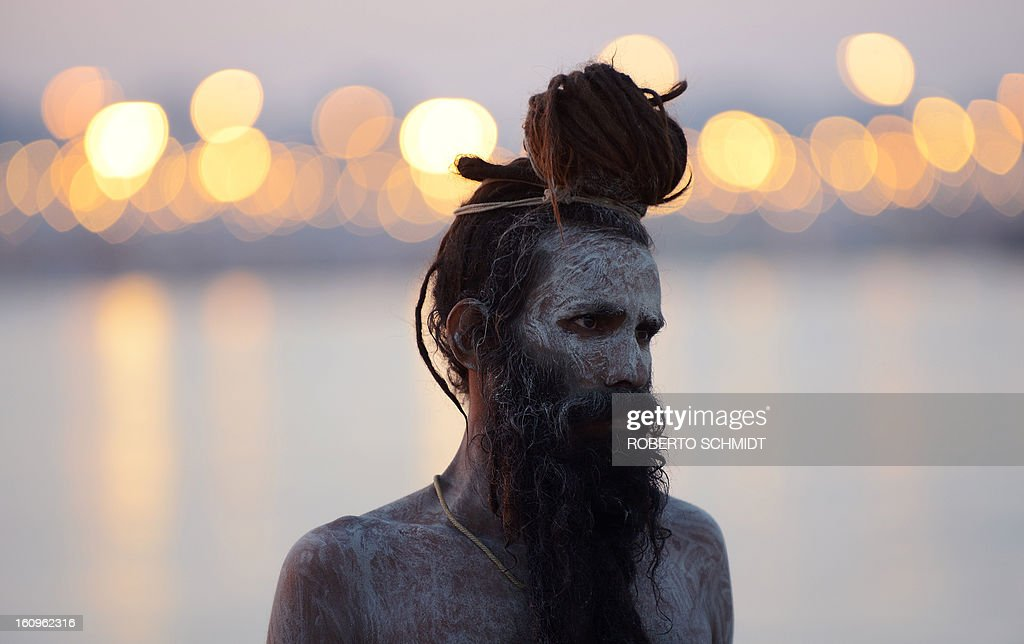 A sadhu - holy man - stands covered in ash after taking a 'holy dip' in the waters of Sangam or confluence of the Yamuna, Ganges and mythical Sarawati rivers at sunset during the Maha Kumbh festival in Allahabad on February 8, 2013. The Kumbh Mela in the town of Allahabad will see up to 100 million worshippers gather over 55 days to take a ritual bath in the holy waters, believed to cleanse sins and bestow blessings.