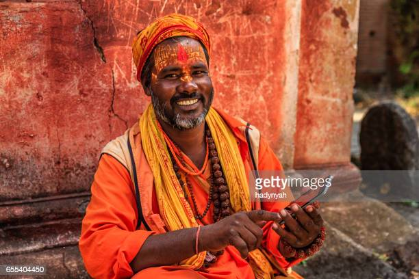Sadhu - indian holyman using mobile phone