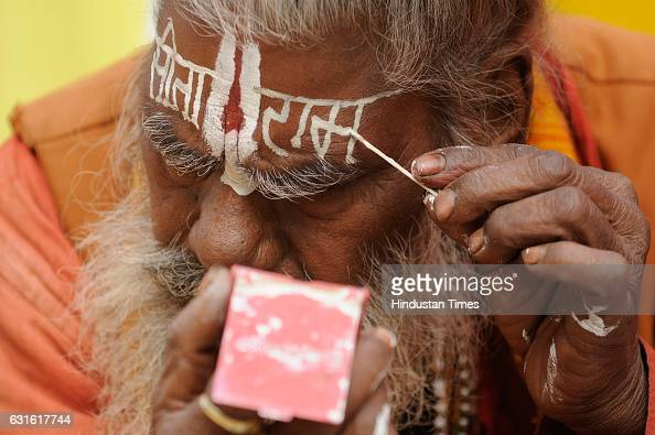 A sadhu is decorating his face before going to Gangasagar festival at Babughat transit camp on January 13 2017 in Kolkata India
