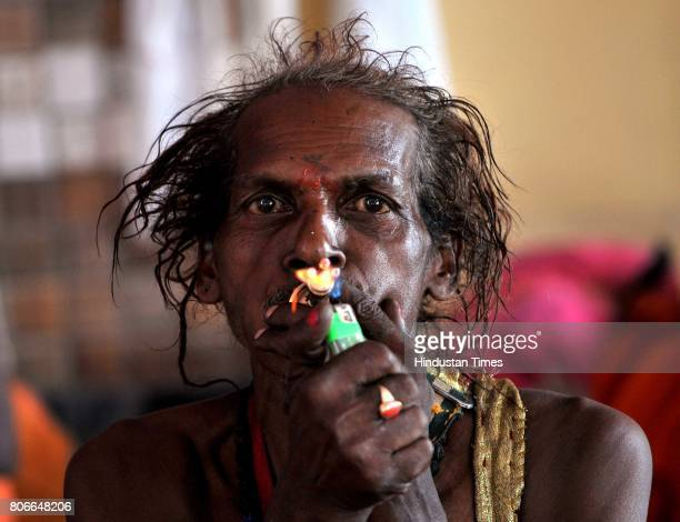 Sadhu or Hindu holy man smokes as he waits to register for the annual Amarnath pilgrimage at Amarnath Yatra base camp on July 3 2015 in Jammu India...