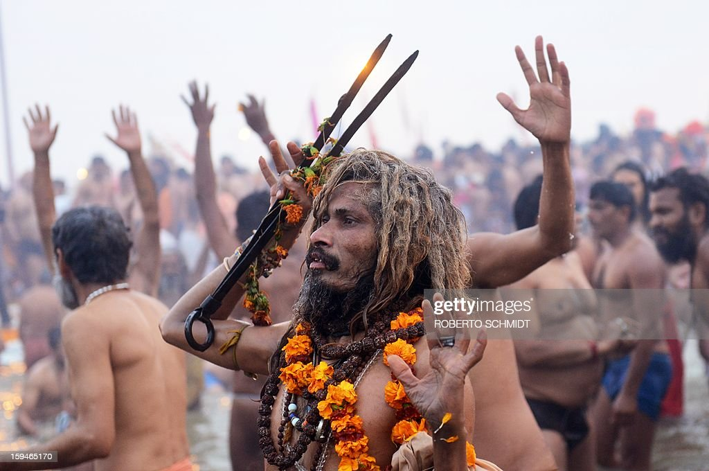 A Sadhu or holy man bathes with others like him at the Sangham or the confluence of the the Yamuna and Ganges rivers during the Kumbh Mela in Allahabad on January 14, 2013. Hundreds of thousands of Hindu pilgrims led by naked, ash-covered holy men streamed into the sacred river Ganges on Monday at the start of the world's biggest religious festival. The Kumbh Mela in the Indian town of Allahabad will see up to 100 million worshippers gather over the next 55 days to take a ritual bath in the holy waters, believed to cleanse sins and bestow blessings. Before daybreak on Monday, a day chosen by astrologers as auspicious, hundreds of gurus, some brandishing swords and tridents, ran into the swirling and freezing waters for the first bath, signalling the start of events.