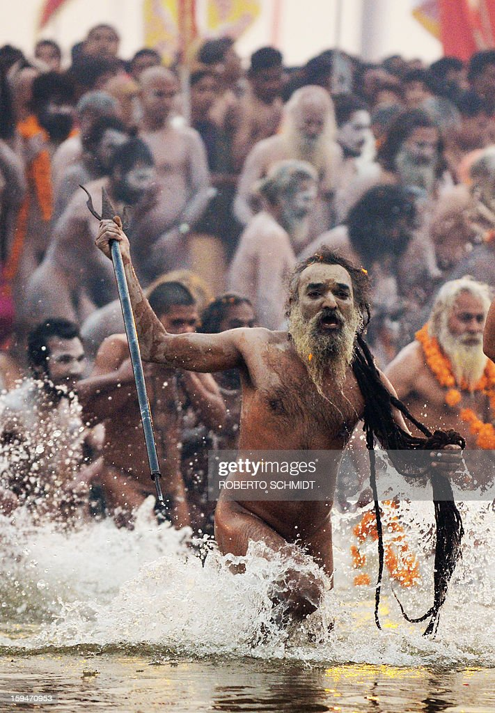 A Sadhu or Holy Man wields a trident as he leads others into the waters of the Sangham or the confluence of the the Yamuna and Ganges rivers during the Kumbh Mela in Allahabad on January 14, 2013. Hundreds of thousands of Hindu pilgrims led by naked, ash-covered holy men streamed into the sacred river Ganges at the start of the world's biggest religious festival. The Kumbh Mela in the Indian town of Allahabad will see up to 100 million worshippers gather over the next 55 days to take a ritual bath in the holy waters, believed to cleanse sins and bestow blessings.