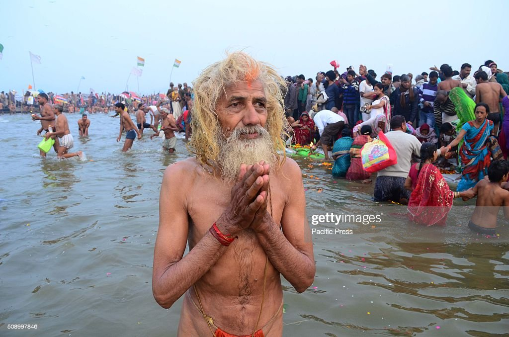 A sadhu performing ritual while taking holydip at Sangam, the confluence of River Ganga Yamuna and mythological Saraswati on the occasion of Maghi Purnima the main holy bathing day during Magh mela festival.