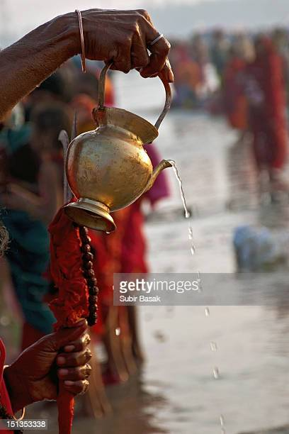 Sadhu pouring water from holy pot.