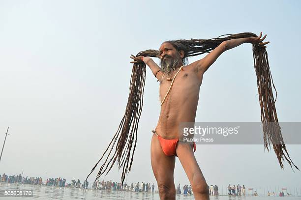 A sadhu pulls up his hair as he takes holy dip during the Magh Mela Hindu devotees gather to bath in the Sangam river confluence during Panchami Magh...