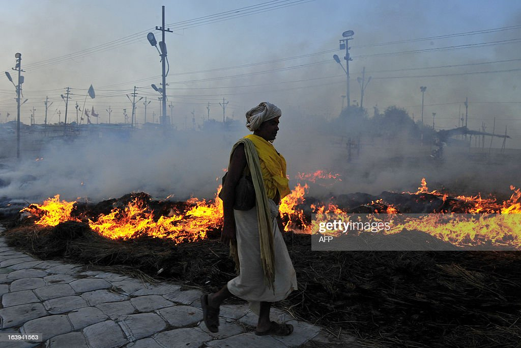 A Sadhu (holy man) returns after taking a holy dip at the Sangam as smoke rises from smouldering husk and dried grass set alight following the conclusion of the Kumbh Mela, in Allahabad on March 18, 2013. The Sangam is a holy bathing site during The Kumbh Mela, which runs from January till March, and takes place every 12 years in Allahabad while smaller events are held every three years in other locations around India. AFP PHOTO/Sanjay KANOJIA