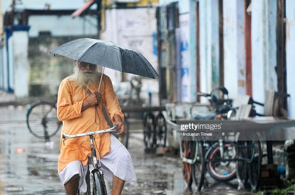 A sadhu rides his bicyle during rainfall on August 27, 2013 in Ayodhya, India.Two days after the failed Parikarma attempt by Vishwa Hindu Parishad (VHP), streets in Ayodhya wears a deserted look with a majority of economical activities limited to certain pockets of the city. Security was on high alert in Ayodhya in wake of Vishwa Hindu Parishad's (VHP) 84 Kosi yatra, which was banned by Uttar Pradesh government.