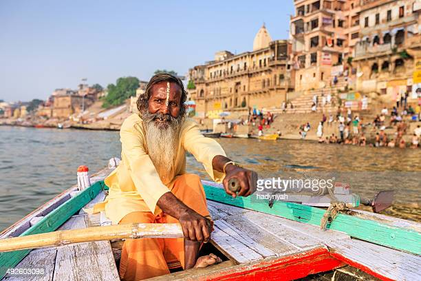 Sadhu rowing boat on the holy Ganges River in Varanasi