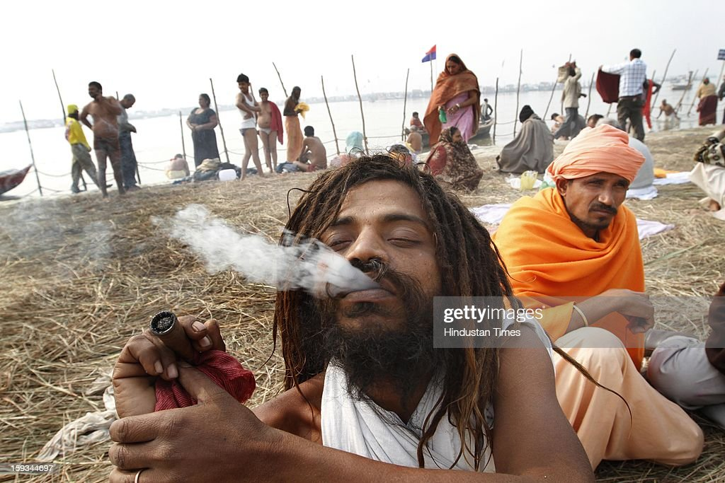 A Sadhu smokes at bank of Sangam ahead of Maha Kumbh Mela (festival), on January 12, 2013 in Allahabad, India. The Kumbh Mela is mass Hindu pilgrimage that alternates between four places Allahabad, Haridwar, Ujjain and Nashik every three years. The current Kumbh Mela is scheduled to take place at Allahabad city in January and February 2013 and is expected to be attended by 60 million devotees.