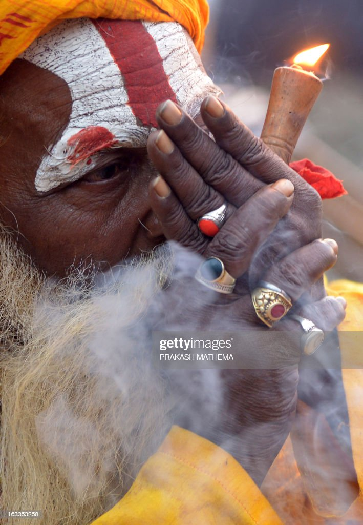 A Sadhu (Hindu holy man) smokes marijuana using a chillum, a traditional clay pipe, as a holy offering for Lord Shiva, the Hindu god of creation and destruction, near the Pashupatinath Temple ahead of the Hindu festival Maha Shivaratri in Kathmandu on March 8, 2013. Hindus mark the Maha Shivratri festival by offering special prayers and fasting. AFP PHOTO / Prakash MATHEMA