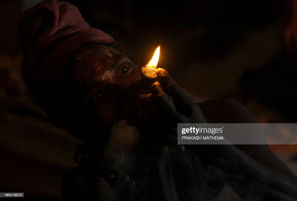 A Sadhu (Hindu holy man) smokes marijuana using a chillum, a traditional clay pipe, as a holy offering for Lord Shiva, the Hindu god of creation and destruction, near the Pashupatinath Temple on the eve of the Hindu festival Maha Shivaratri in Kathmandu on March 9, 2013. Hindus mark the Maha Shivratri festival by offering special prayers and fasting. AFP PHOTO / Prakash MATHEMA