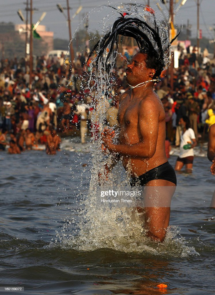 A Sadhu takes a holy dip at the Sangam, confluence of rivers Ganga, Yamuna and mythical Saraswati on the occasion of Paush Purnima on January 27, 2013 in Allahabad, India. Millions of Hindu pilgrims are expected to take part in the large religious congregation of a period of over a month on the banks of Sangam during the Maha Kumbh Mela in January 2013, which falls every 12th year.