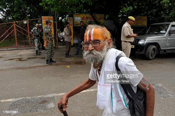 A sadhu walks amidst heavy security to offer prayers on August 28 2013 in Ayodhya India Three days after Vishwa Hindu Parishad field Parikarma...