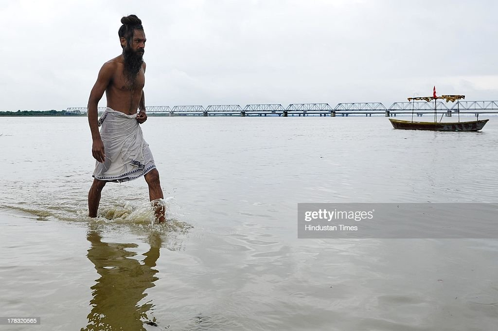 A sadhu walks at Saryu ghat after taking a holy dip on August 28, 2013 in Ayodhya, India. Three days after Vishwa Hindu Parishad (VHP) field Parikarma attempt, Ayodhya saw a heavy presence of security personnel amid Janmashtmi celebrations.