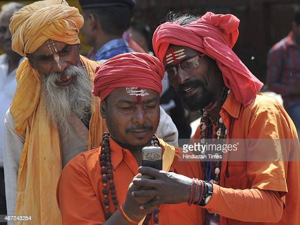 Sadhus from Mathura clicking each others pictures through mobile as they have come to participate in the Yamuna Muktikaran Protest to demand that the...