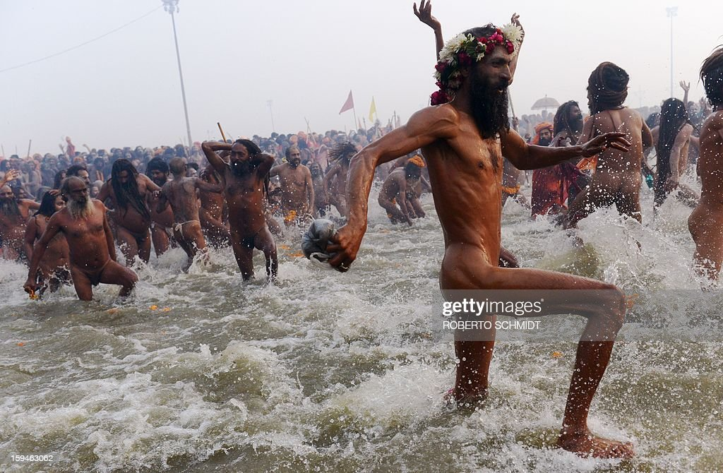 Sadhus or holy man run into the Sangham or the confluence of the the Yamuna and Ganges rivers during the Kumbh Mela in Allahabad on January 14, 2013. Hundreds of thousands of Hindu pilgrims led by naked, ash-covered holy men streamed into the sacred river Ganges on Monday at the start of the world's biggest religious festival. The Kumbh Mela in the Indian town of Allahabad will see up to 100 million worshippers gather over the next 55 days to take a ritual bath in the holy waters, believed to cleanse sins and bestow blessings. Before daybreak on Monday, a day chosen by astrologers as auspicious, hundreds of gurus, some brandishing swords and tridents, ran into the swirling and freezing waters for the first bath, signalling the start of events.