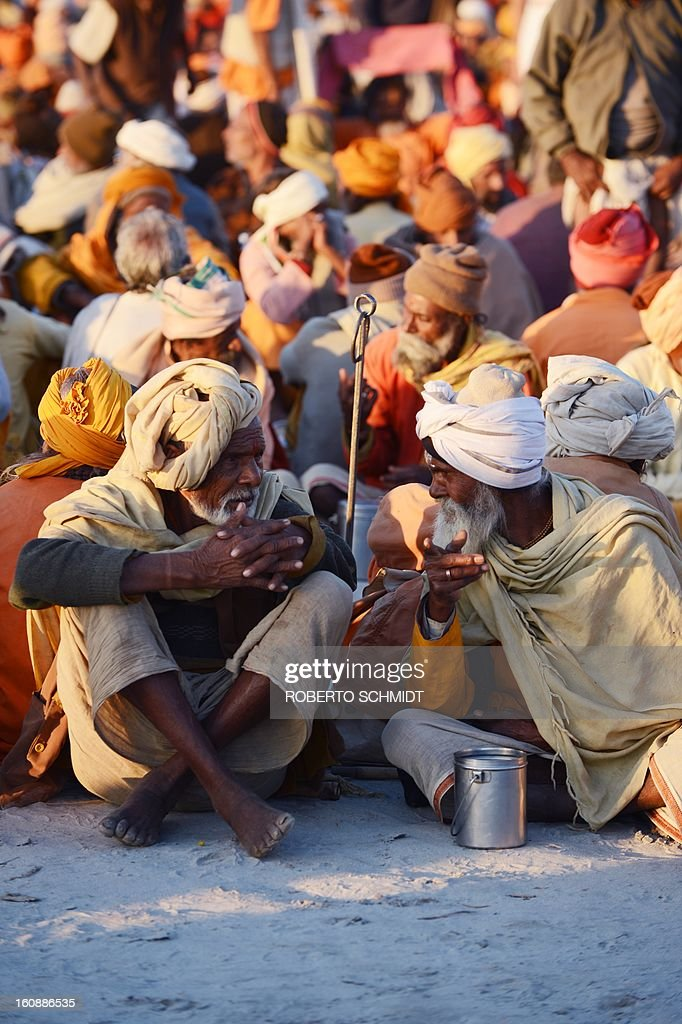 Sadhus or holy men wait to be fed near he confluence of the Yomuna and the Ganges river at the Sangam in the early evening as they wait to be served a free meal organized by an ashram during the Maha Kumbh festival in Allahabad on February 7, 2013. The Kumbh Mela in the town of Allahabad will see up to 100 million worshippers gather over 55 days to take a ritual bath in the holy waters, believed to cleanse sins and bestow blessings.