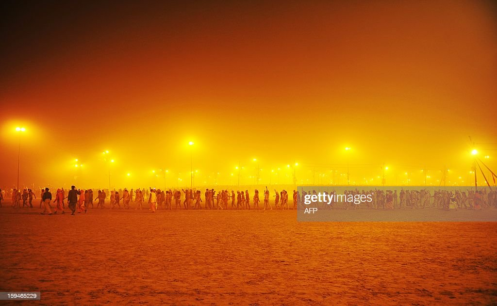 Sadhus or holy men walk in a procession towards the Sangham or the confluence of the the Yamuna and Ganges rivers to bathe before sunrise during the Kumbh Mela in Allahabad on January 14, 2013. Hundreds of thousands of Hindu pilgrims led by naked, ash-covered holy men streamed into the sacred river Ganges on Monday at the start of the world's biggest religious festival. The Kumbh Mela in the Indian town of Allahabad will see up to 100 million worshippers gather over the next 55 days to take a ritual bath in the holy waters, believed to cleanse sins and bestow blessings. Before daybreak on Monday, a day chosen by astrologers as auspicious, hundreds of gurus, some brandishing swords and tridents, ran into the swirling and freezing waters for the first bath, signalling the start of events.